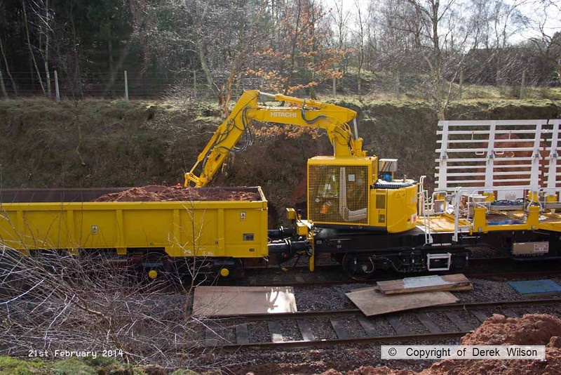 140221-001     The Hitachi Zaxis 135 US hydraulic excavator fitted to HOPS MPV no 99 70 9131 006-7, seen digging stanchion bases at Ollerton on the High Marnham Test Track. The spoil wagon is a JNA 'Falcon' no 29024 which was repainted & prepared for use with the consist at Tuxford.