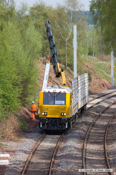 140424-019     The latest section of the HOPS electrification train to visit the RIDC for commissioning trials is HOPS MPV no 99 70 9131 013-3 which is fitted with a crane for lifting the masts into position, and mast carrying wagon, type KFA no 99 70 9131 012-5. They are seen at work erecting masts near School Lane, Ollerton.