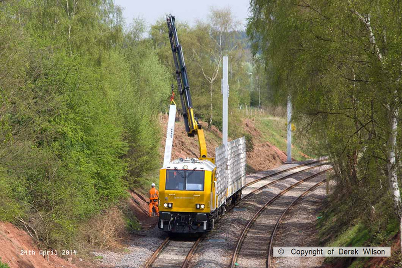140424-021     The latest section of the HOPS electrification train to visit the RIDC for commissioning trials is HOPS MPV no 99 70 9131 013-3 which is fitted with a crane for lifting the masts into position, and mast carrying wagon, type KFA no 99 70 9131 012-5. They are seen at work erecting masts near School Lane, Ollerton.