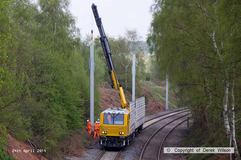 140424-024     The latest section of the HOPS electrification train to visit the RIDC for commissioning trials is HOPS MPV no 99 70 9131 013-3 which is fitted with a crane for lifting the masts into position, and mast carrying wagon, type KFA no 99 70 9131 012-5. They are seen at work erecting masts near School Lane, Ollerton.