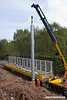 140424-012     The latest section of the HOPS electrification train to visit the RIDC for commissioning trials is HOPS MPV no 99 70 9131 013-3 which is fitted with a crane for lifting the masts into position, and mast carrying wagon, type KFA no 99 70 9131 012-5. They are seen at work erecting masts near School Lane, Ollerton.