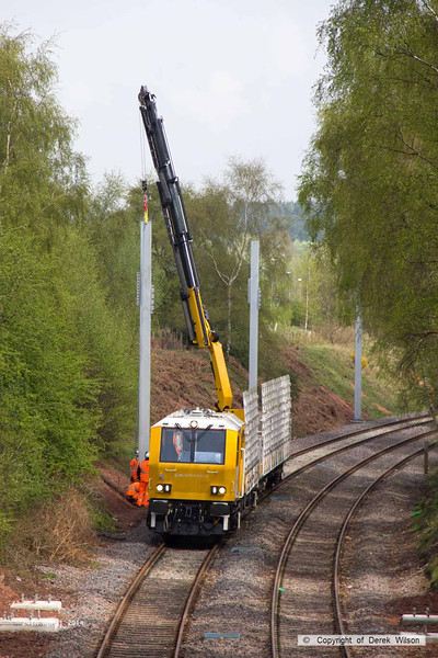 140424-027     The latest section of the HOPS electrification train to visit the RIDC for commissioning trials is HOPS MPV no 99 70 9131 013-3 which is fitted with a crane for lifting the masts into position, and mast carrying wagon, type KFA no 99 70 9131 012-5. They are seen at work erecting masts near School Lane, Ollerton.
