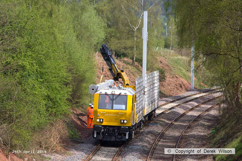 140424-018     The latest section of the HOPS electrification train to visit the RIDC for commissioning trials is HOPS MPV no 99 70 9131 013-3 which is fitted with a crane for lifting the masts into position, and mast carrying wagon, type KFA no 99 70 9131 012-5. They are seen at work erecting masts near School Lane, Ollerton.