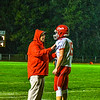 North Middlesex head coach Sandy Ruggles chats with his quarterback, Joe Haskins,  in the driving rain during the fourth quarter of Friday's game. Nashoba Valley Voice/Ed Niser