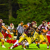 North Middlesex's Xavier Marty clings on to the legs of Algonquin running back Max Cerasoli. Nashoba Valley Voice/Ed Niser