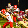 North Middlesex quarterback Joe Haskins high-steps an Algonquin defender as running back Jake Hachey clears the path. Nashoba Valley Voice/Ed Niser