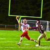 North Middlesex quarterback Joe Haskins throws on the run as he is pressured by Algonquin defensive lineman Colin Robinson. Nashoba Valley Voice/Ed Niser