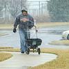Gary Simpson employee puts down salt on selected walkways in Heritage Shores