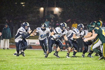 JOSH KAUFMANN, St. Albans Messenger Essex running back Phil Wilson takes a handoff while Kevin Svarczkopf (33), David fraser (72) and Marshall Murphy (64) try to create some running room at the rainy Collins-Perley Sports Center in St. Albans on Friday night.