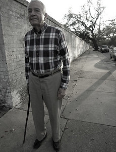 A nice older gentleman walking in a neighborhood near St. Charles. Over the wall on his right is a beautiful New Orleans cemetery.