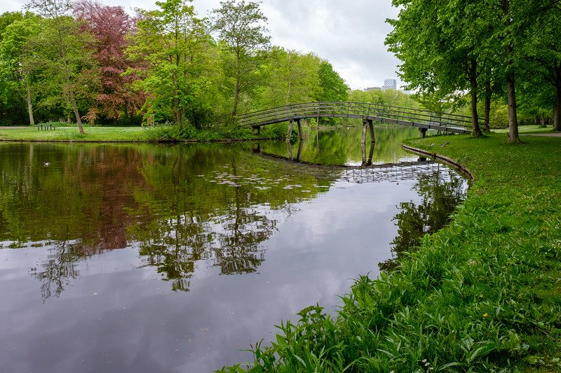 Reflection of small arch bridge over tree lined lake in spring.