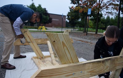 Sunbra Sunderaswaren (left), an engineer at FCA and Tina Hornek, a transmission engineer for FCA, working on a picnic table at the FCA volunteer event for World Habitat Day at the Walter P. Chrysler Museum on Monday, Oct. 3 2016.