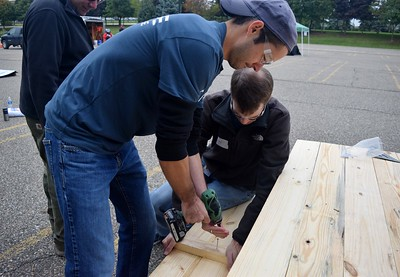 Volunteers begin working on picnic tables at the FCA volunteer event for World Habitat Day at the Walter P. Chrysler Museum on Monday, Oct. 3 2016.
