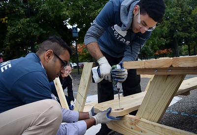 Sunbra Sunderaswaren (left), an engineer at FCA and Freyhan Daruwalla, a transmission engineer at FCA working on a picnic table at the FCA volunteer event for World Habitat Day at the Walter P. Chrysler Museum on Monday, Oct. 3 2016.