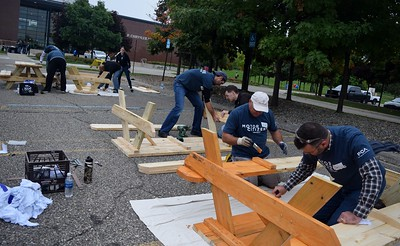 Volunteers begin painting picnic tables at the FCA volunteer event for World Habitat Day at the Walter P. Chrysler Museum on Monday, Oct. 3 2016.