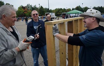Jerry Esper (left), powertrain engineer with FCA, Randy Kokoska, design release engineer with FCA and Jeff Walz, test engineer with FCA work on building a shed at the FCA volunteer event for World Habitat Day at the Walter P. Chrysler Museum on Monday, Oct. 3 2016.