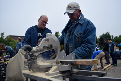 Volunteers cutting wood for wheelchair ramps at the FCA volunteer event for World Habitat Day at the Walter P. Chrysler Museum on Monday, Oct. 3 2016.