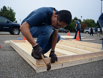 Steve Tang, motion controller at FCA, hammers a nail while working on building a shed at the FCA volunteer event for World Habitat Day at the Walter P. Chrysler Museum on Monday, Oct. 3 2016.