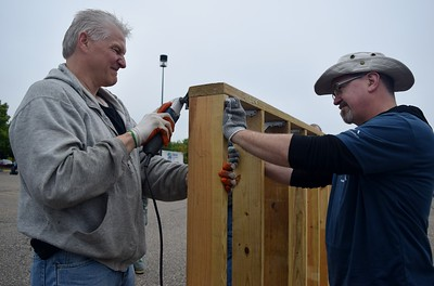 Jerry Esper (left), powertrain engineer with FCA and Jeff Walz, test engineer with FCA work on building a shed at the FCA volunteer event for World Habitat Day at the Walter P. Chrysler Museum on Monday, Oct. 3 2016.