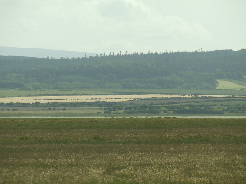Looking across the tidal flats towards the Northumberland coast from the Causeway Road on Lindisfarne. The poles in the distance mark the route of the pilgrims that travelled to the island during the middle ages, and the route can still be followed at low tide. In middle distance beyond the poles is the A1