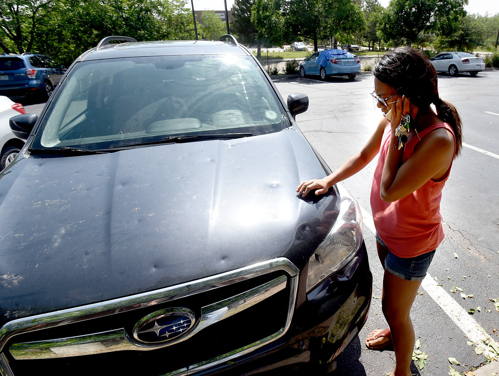 . Marielle Galanto checks out the hail damage to her Subaru while on the photo  to the insurance company on Tuesday at the Marriott Residence Inn in Louisville.  Cliff Grassmick / Staff Photographer/ June 19, 2018