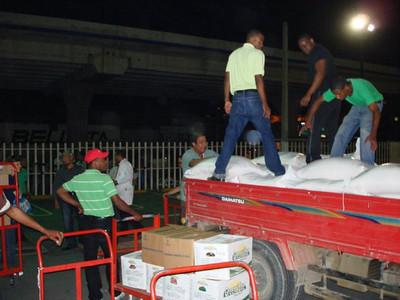 Loading tons of food for transport to Port-au-Prince. Ruokatarvikkeiden lastaus Haitiin kuljetusta varten.