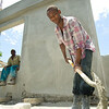 A worker uses a shovel to mix concrete at what will soon be the new Immigration and Customs Office near the town of Belladere, in central Haiti. The site is part of a larger complex of administrative buildings for Haitian customs and police officials  being built by PADF through the Haiti Border Stabilization and Reconstruction Initiative (HBI), which has also been working to sensitive local resident son a range of environmental, migration and human rights issues.