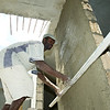 A worker smoothes concrete on a wall of the Immigration and Customs Office near the town of Belladere, in central Haiti. The site is part of a larger complex of administrative buildings for Haitian customs and police officials  being built by PADF through the Haiti Border Stabilization and Reconstruction Initiative (HBI).