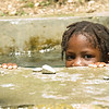 A young girl swims in a cool pool of clear spring water, after a PADF water project, funded by the Government of Taiwan, restored water to the community of Mahotiere in 2010. Through the project, PADF reached more than 10,000 people in the area with potable water by building two new water systems to replace existing systems damaged by recent hurricanes and the 2010 earthquake.