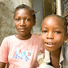 Two girls in the Delmas 32 neighborhood of Port au Prince look on as engineers sub contracted by PADF inspect their damaged home for repair possibilities. Through PADF support, more than 248,000 homes were initially assessed for damages. Those that can will eventually be repaired.