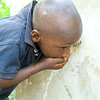 A young boy drinks clean drinking water from a fountain in the village of Gaillard, one of several rehabilitated by a PADF water project near the town of Cayes Jacmel in southeastern Haiti. Clean water is essential for both health and hygiene in Haiti, and the water project, funded by the Government of Tiaiwan, reaches more than 10,000 people with potable spring water.