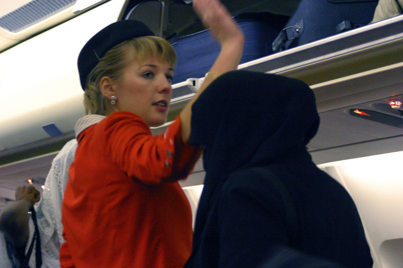A veiled muslim lady passes by the flight attendent.