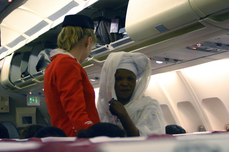 A contrast between the western Royal Jordan flight attendent and the african lady passing by her.  I found the african men and women most fascinating iin how they dressed and did their hair.