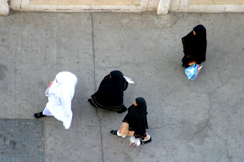Pedestrian traffic.  Here the women are dressed according to Saudi custom and only expose their faces, hands and feet.