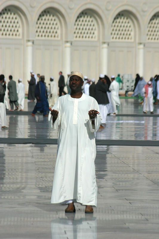 An african man praying before the mosque.  I noticed him and then looked around and saw the he was getting a videotape made of his visit to Medina!