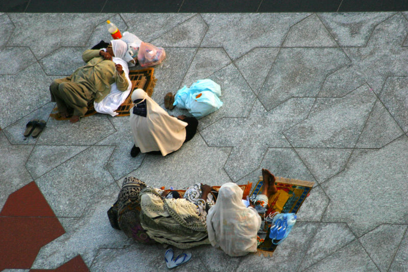 A group of women on their prayer rugs waiting for prayers to start.