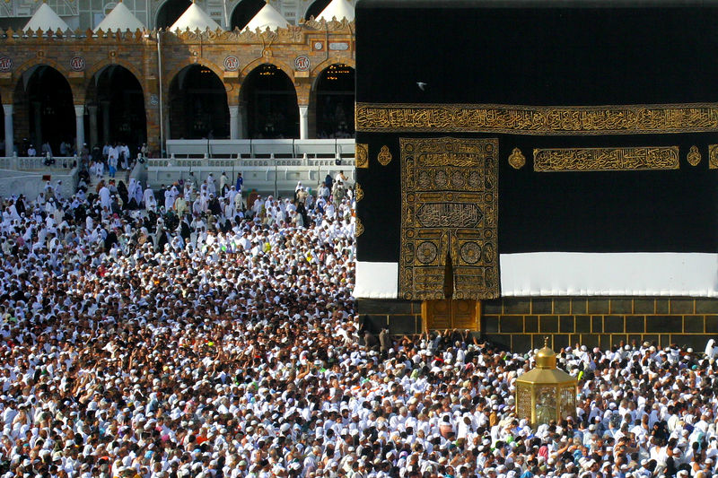 """This corner of the Kaaba defines the starting line to do the tawaf or rounds.  When the pilgrims reach this point they lift their hands towards the black stone palms away.  If you view this picture as the original by clicking on the picture and picking """"O"""", you can zoom in on the hajis at the corner lifting up their arms."""