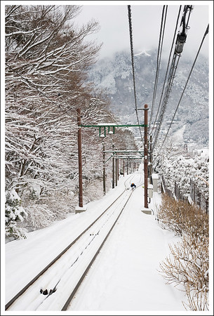 The cable car tracks in the snow.  A maintenance worker is clearing the snow from the switch mechanism.