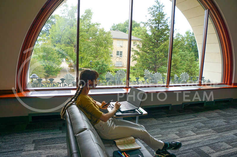 A college girl doing her homework and in the second level open study area. A great day to be in front of the windows. 15 September 2020. Haley Jacques || Collegian Media Group