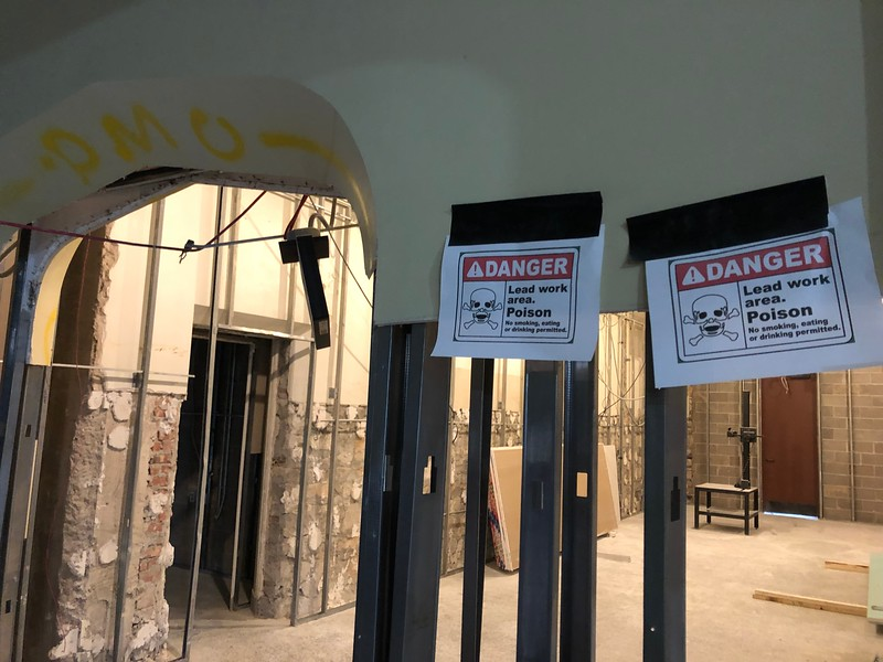 Taped signs advise construction crew members that this area of Hale Library is a lead work area on May 17, 2019. (Dene Dryden | Collegian Media Group)