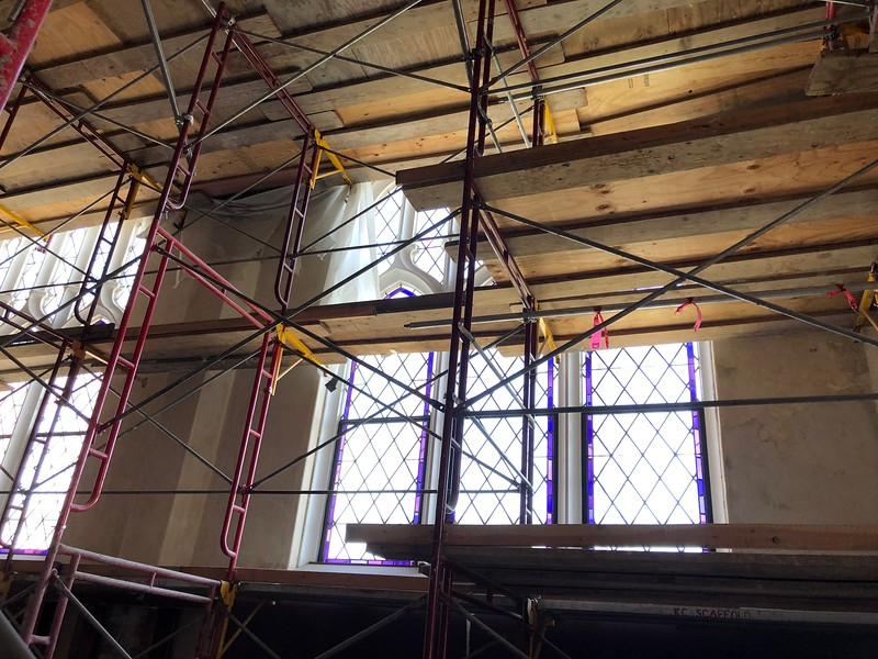 Purple stained glass peeks out through the red, brown and gray construction clutter in Hale Library's Great Room on May 17, 2019. (Dene Dryden | Collegian Media Group)