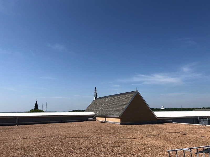 The roof of Hale Library, where the bell tower of Anderson Hall, the old campus radio towers and a Manhattan water tower can be seen. Photo taken on on May 17, 2019. (Dene Dryden | Collegian Media Group)