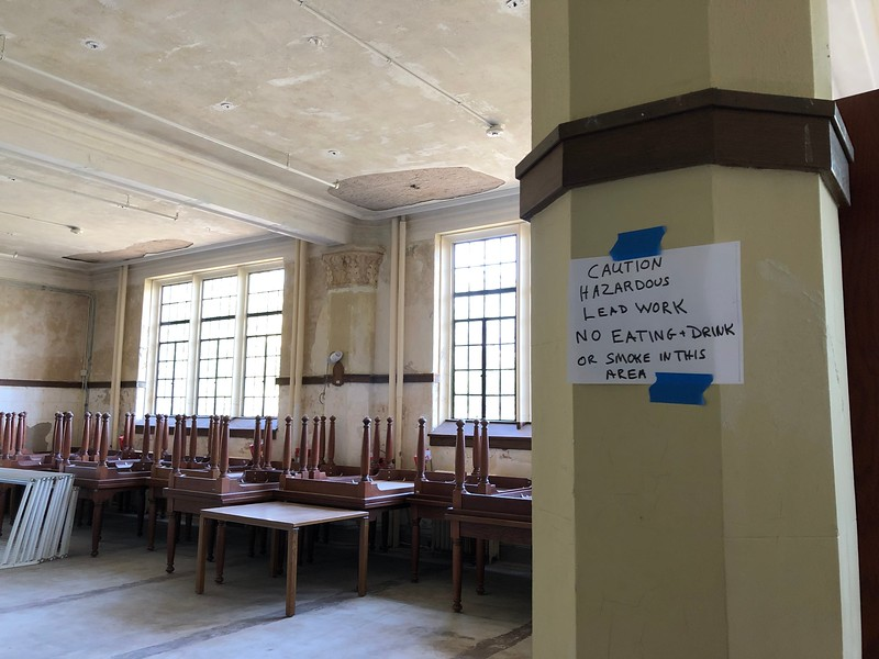With tables stacked around the edges of the room, a sign affixed to a column in Hale 212 warns construction workers on May 17, 2019. (Dene Dryden | Collegian Media Group)
