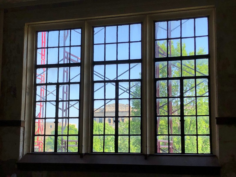 Through the window panes and scaffolding outside Hale Library, Calvin Hall is visible to the north. Photo taken in Hale 212 on May 17, 2019. (Dene Dryden | Collegian Media Group)