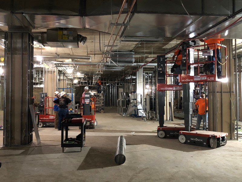 Workmen install piping in the ceiling of Hale Library's first floor on May 17, 2019. (Dene Dryden | Collegian Media Group)