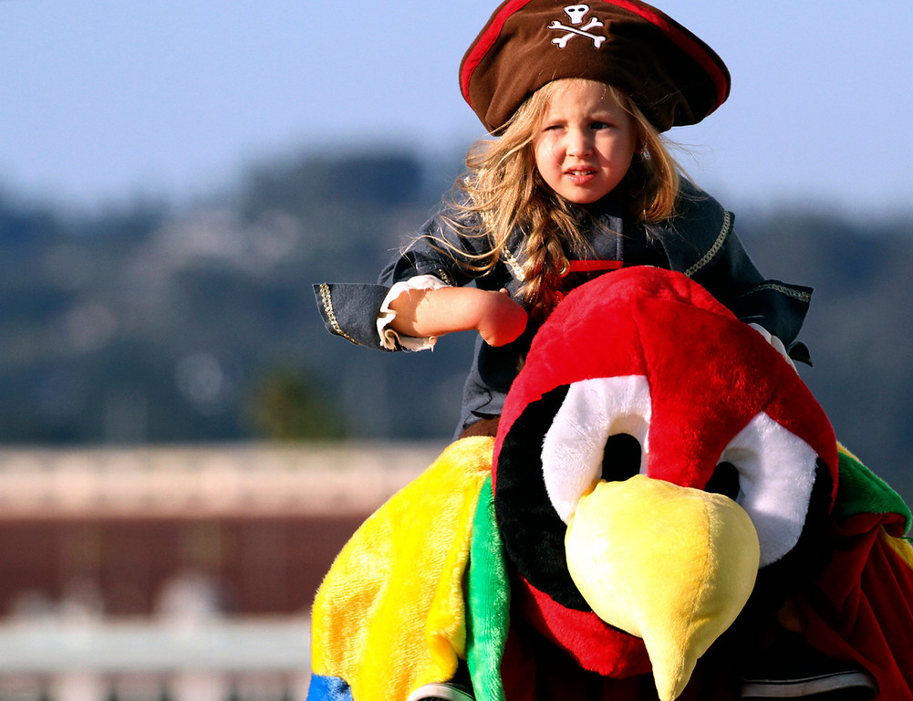 . Pirate Isla Guzman-Sadler sits atop the shoulders of her father Nick, who was dressed as a parrot as she trick-or-treats at the Santa Cruz Municipal Wharf Tuesday. (Shmuel Thaler -- Santa Cruz Sentinel)