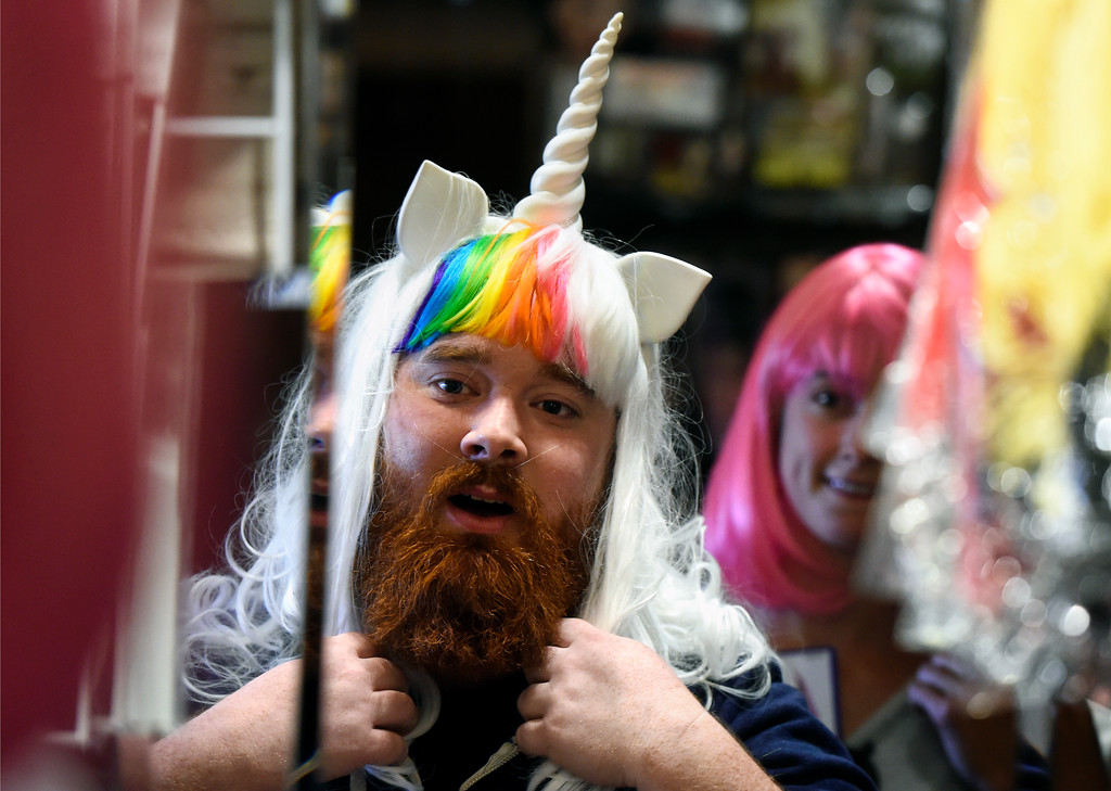 . Dylan Ham, left, tries on a Unicorn wig as Sarah Niemeyer looks at him while they both shopped for a Halloween costume on Wednesday at The Ritz Costumes on Walnut Street in Boulder. For more photos of people shopping for costumes at The Ritz go to dailycamera.com Jeremy Papasso/ Staff Photographer 10/25/2017