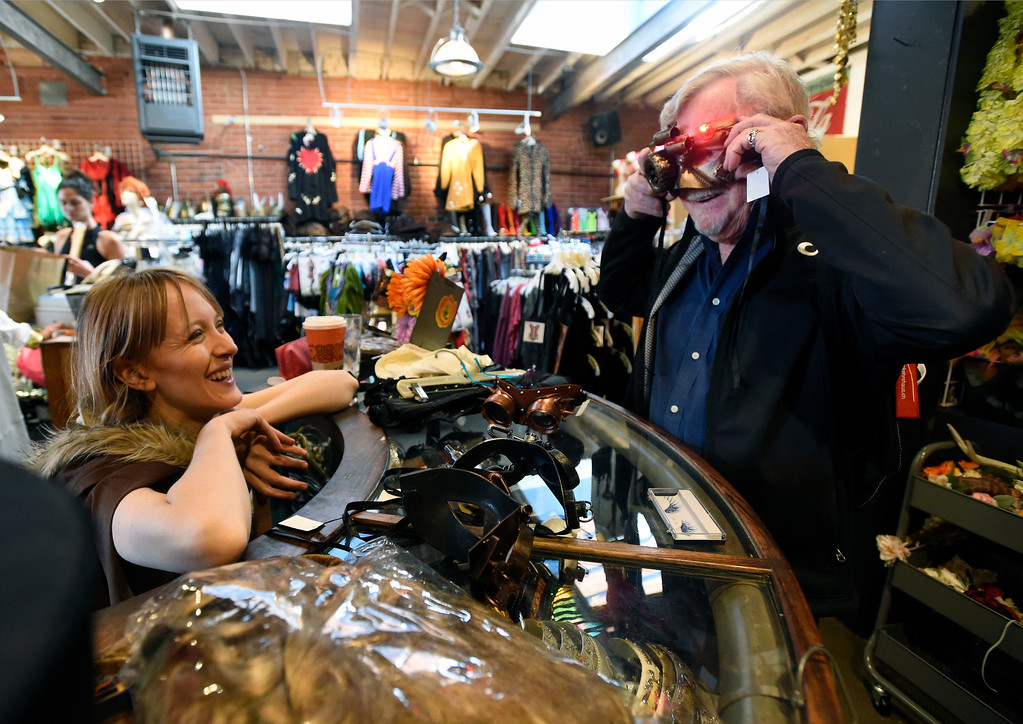 . Employee Margret Skowronski, left, laughs as Dean Fogerty tries on a mask while he shopped for a Halloween costume on Wednesday at The Ritz Costumes on Walnut Street in Boulder. For more photos of people shopping for costumes at The Ritz go to dailycamera.com Jeremy Papasso/ Staff Photographer 10/25/2017