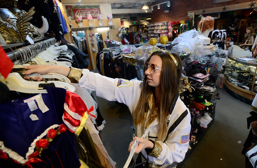 . Employee Lauren Owting hangs Halloween costumes on a rack on Wednesday at The Ritz Costumes on Walnut Street in Boulder. For more photos of people shopping for costumes at The Ritz go to dailycamera.com Jeremy Papasso/ Staff Photographer 10/25/2017