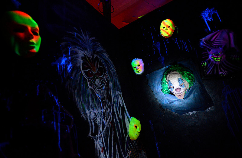 Brandon Harrington, founder of Harrington Arts Alliance, poses for a photo wearing a clown mask blending in with the black light area Monday, Oct. 16, 2016, at the HAAunted House at 1601 N. Lincoln Ave. in Loveland.   (Photo by Jenny Sparks/Loveland Reporter-Herald)